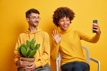 Wall Mural - Happy interracial couple take selfie on mobile phone wave hello gesture make online video call sit on comfortable chairs isolated over yellow background. Mixed race female and male pose for photo