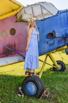 Cute woman stands on an abandoned plane. A woman with a wreath of flowers on her head