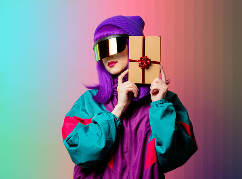 Style woman in VR glasses and 80s tracksuit with gift box