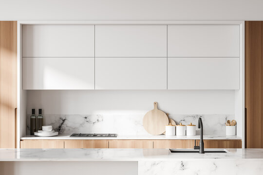White and wooden kitchen with cupboards, close up