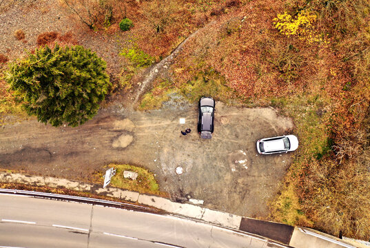 Vertical aerial view of two cars and unrecognizable people on a gravel parking lot with a large fir tree at the edge of the country road