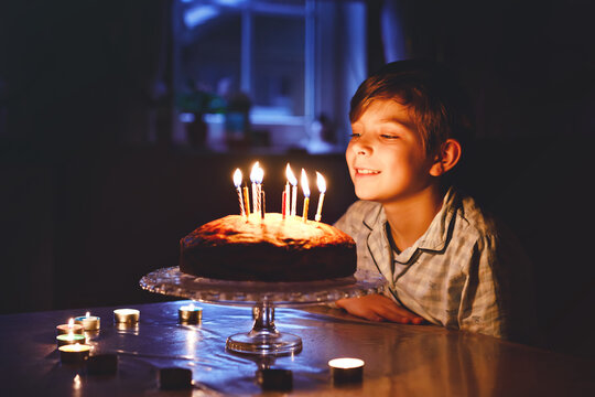 Adorable happy blond little kid boy celebrating his birthday. Child blowing candles on homemade baked cake, indoor. Birthday party for school children, family celebration
