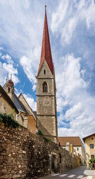 The high bell tower of the parish church of Santa Maria Assunta (in German Pfarrkirche Mariä Himmelfahrt) in Silandro, South Tyrol, Italy, under a beautiful sky