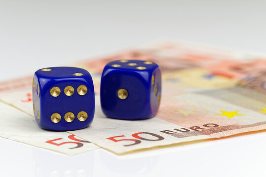 Two blue dices and euro banknotes on white background
