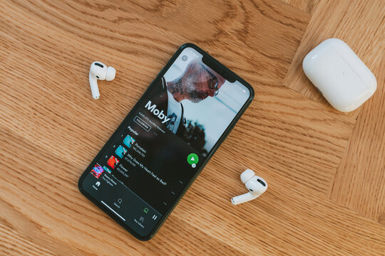 Spotify app on the screen and Apple Airpods Pro