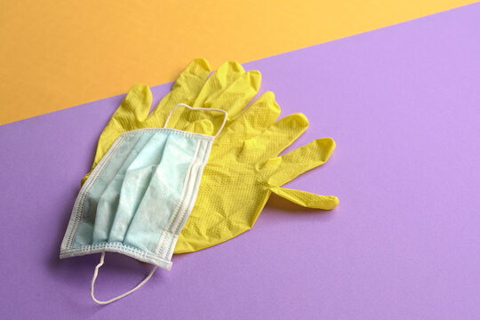Hand gloves and medical face mask on purple  and yellow background.