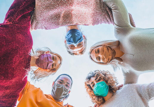 Multiethnic Group of Friends with face mask in Circle - Diverse People of Different Ethnicities Smiling and Looking Up at the Camera in coronavirus time - Concepts of friendship, teamwork