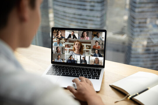 Shoulder back view female businesswoman looking at laptop screen, briefing discussing working issues with diverse multiracial colleagues by video call app, happy people communicating online distantly.