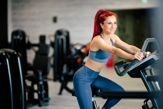 Fit active woman in the gym, working out on stationary bicycle at local gym.  Fitness and bodybuilding concept
