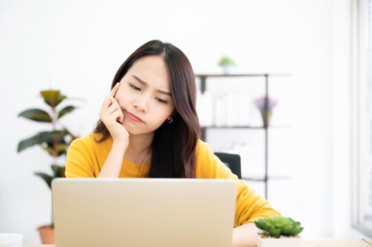 Asian young woman seriously working on computer laptop in house. She thinking find solution problem of work