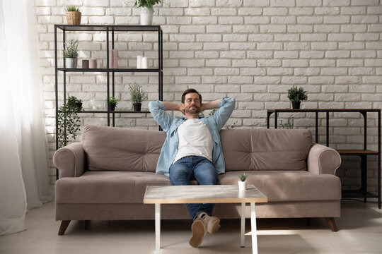 Peaceful young man relaxing meditating on comfortable sofa with folded hands behind hand, breathing fresh air, daydreaming napping enjoying calm mindful lazy weekend moment alone in modern living room