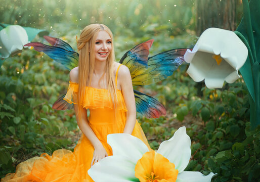 Beautiful happy woman fairy nymph sitting on forest. Magical fantasy wings costume pixie butterflies. Elf girl princess long yellow dress. blond hair smiling face. Summer nature tree, green grass