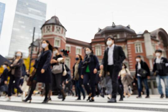 意図的にピントをぼかした東京駅前の横断歩道を渡るマスク姿のビジネスマンたち