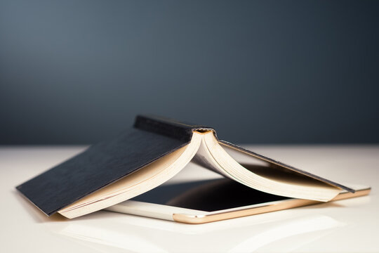 Opened Book Above Digital Tablet