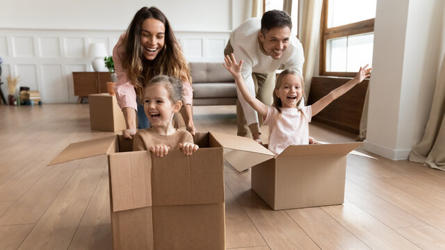 Cheerful adorable screaming girls sit inside of big carton boxes during race competition play with parents at new modern home at move day. Bank loan for young family, active games with kids concept