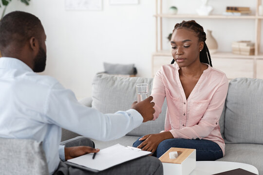 Psychotherapist Comforting Upset African American Lady During Therapy Session At Office
