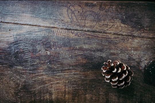 Fond en bois vieilli avec une pomme de pin dans un angle - Arrière plan ambiance saison d'hiver avec espace vide