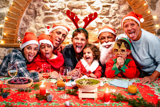 Funny selfie pic of multi generation large family with santa hats having fun at Christmas fest house party - Winter holiday xmas concept with grand parents and children eating together - Vivid filter