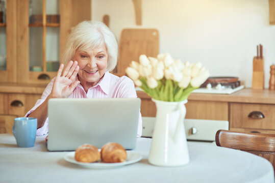 Smiling senior woman waving at screen while chatting during video call