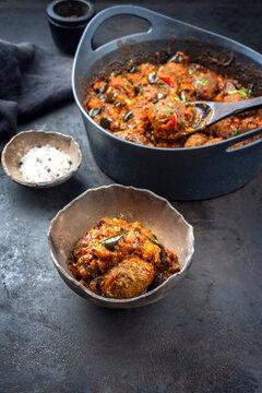 Traditionelle amerikanisches slow cooked American Tex Mex Fleischbällchen mit Auberginen und Hackfleisch vom Rind in würziger Sauce serviert als close-up in einer rustikalen Design Schale