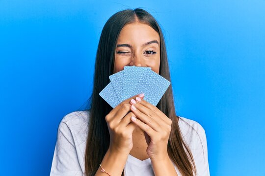 Young hispanic woman playing gambling poker covering face with cards winking looking at the camera with sexy expression, cheerful and happy face.