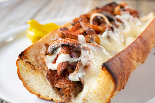 A closeup view inside a grilled mushroom and steak hoagie sandwich.