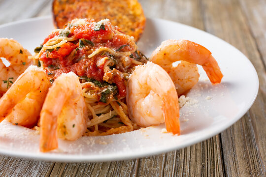 A view of a plate of angel hair pasta with shrimp.