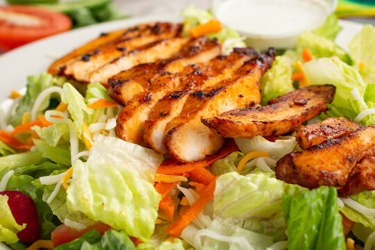 A closeup view of a grilled chicken salad.