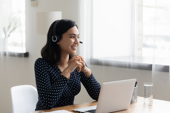 Smiling Asian businesswoman wearing headset using laptop, looking to aside, dreaming about new job opportunities, happy woman student watching webinar, listening to lecture, studying, home office