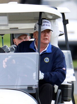 U.S. President Donald Trump drives a golf cart at the Trump National Golf Club in Sterling