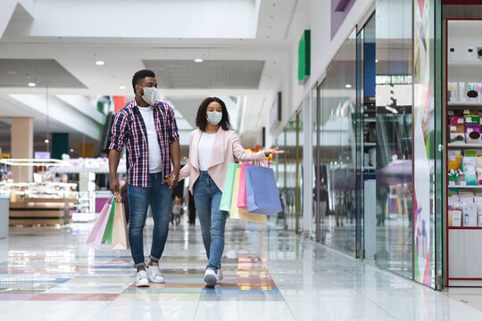 Young black couple wearing protective medical face mask walking in shopping mall