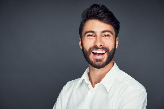 Portrait of successful young man smiling isolated on dark background