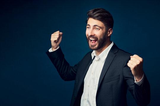 Successful businessman shouting against dark blue background