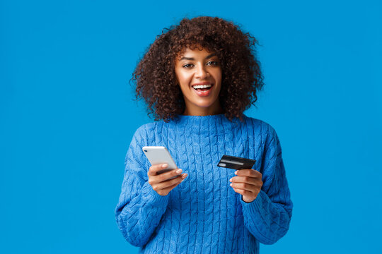 Cheerful good-looking smiling african-american woman buying online, shopping during discounts holiday season, smiling, holding smartphone and credit card, standing blue background