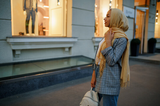 Arab girl in hijab looking on showcase in downtown