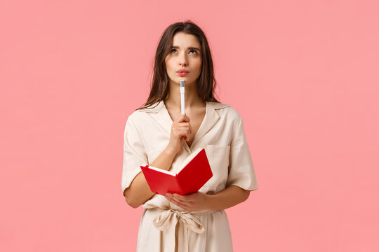 Thoughtful and creative young woman making list, pouting and looking up pensive and inspired, holding red notebook and pen, create new poem or prepare for exam, thinking over pink background