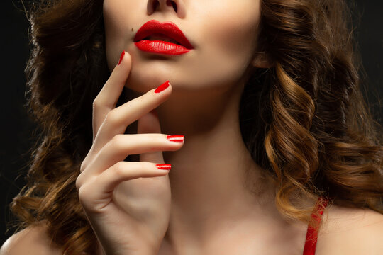 Beautiful young model with red lips and red manicure hild white sheet.