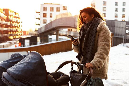 Woman with pram using phone, Norway