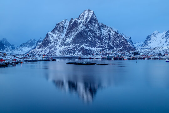 Lofoten islands, Norway. Colorful winter landscape in blue hour with fishing village and snowy mountains reflected on water.