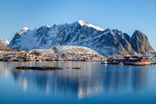 Lofoten islands, Norway. Colorful winter landscape at sunset. Fishing village and showy mountains reflected in water.