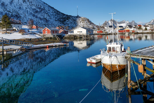 Lofoten islands, Norway. Fishing boats in the harbour, red rorbu  houses, mountains in the background.