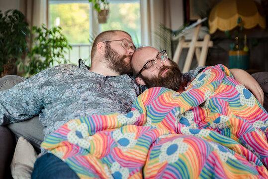 Male couple sleeping on sofa, Sweden