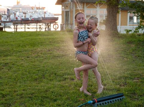 Girls playing with water sprinkler in garden, Sweden
