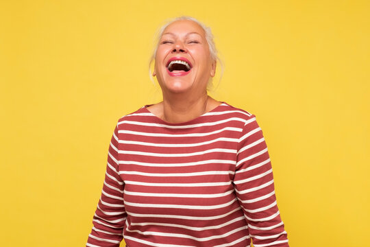 Middle age caucasian woman smiling and laughing hard out loud because funny joke.