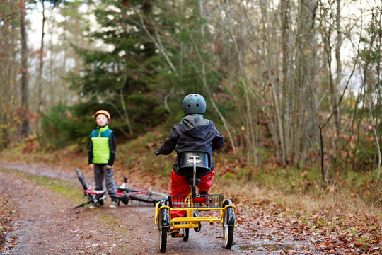 Boys cycling through forest, Sweden