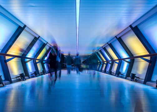 Long Exposure of commuters walking through crossrail canary wharf station in London, UK