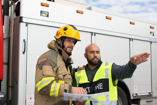 Security guard and firefighters discussing plan, Sweden