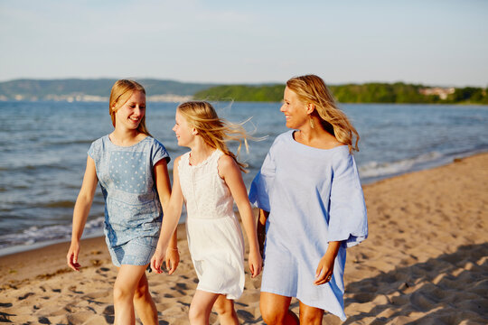 Mother with daughters walking on beach, Sweden