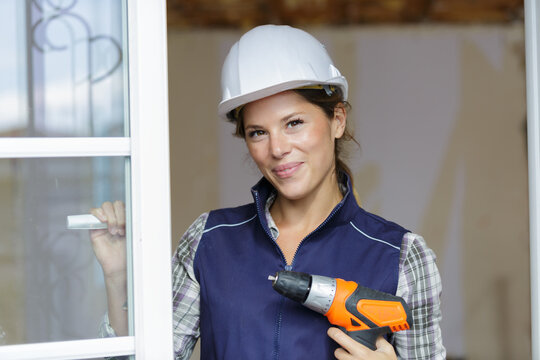 woman using electronic drill installing door