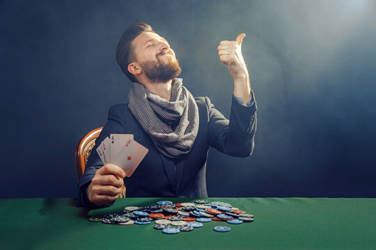 Happy poker player winning and holding a pair of aces.